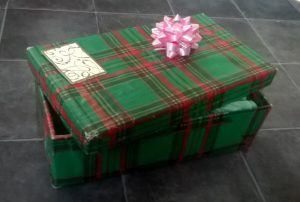 Reusable gift box made from a shoe box covered in wrapping paper - it's seen better days, but you get the idea
